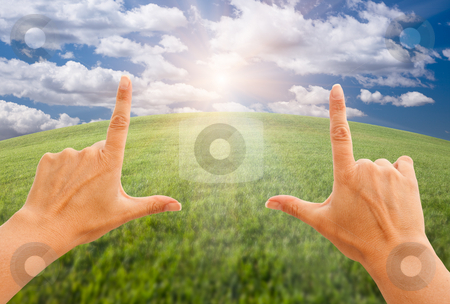 Female Hands Making a Frame Over Grass and Sky stock photo, Female Hands Making a Frame Over Arched Horizon of Grass Field, Sunlight, Clouds and Sky. by Andy Dean