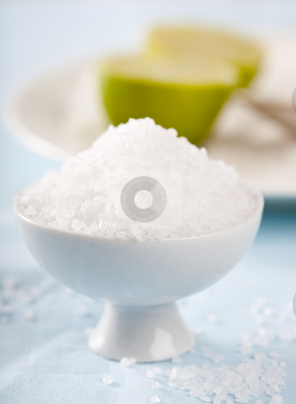 Salt stock photo, Pile of sea salt on blue tablecloth with lime in the background by Simone Van den Berg
