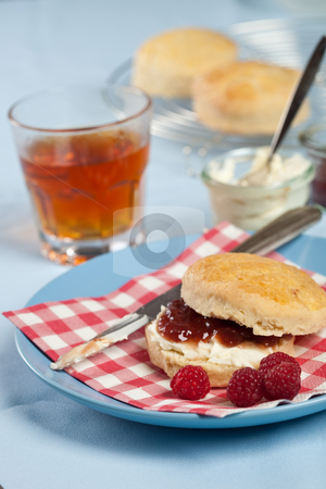 Scones with cream and jam stock photo, Delicious scone with clotted cream and raspberry jam by Simone Van den Berg