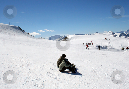 Skiers on Alpine ski slope stock photo, Two skiers resting on Alpine ski slope with people skiing in background. by Martin Crowdy