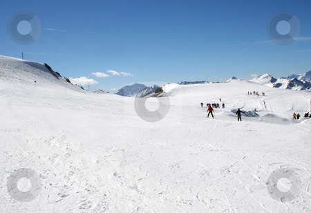 Skiers on Alpine ski slope stock photo, Scenic view of skiers on Alpine ski slope with people skiing in background. by Martin Crowdy