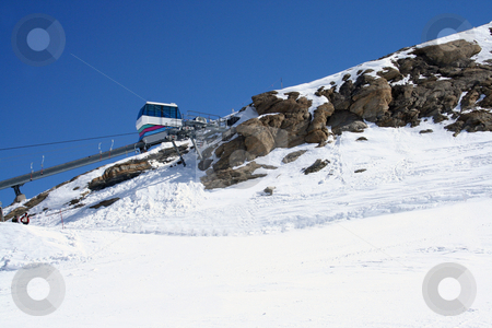 Ski lift on snowy mountainside stock photo, Scenic view of ski lift on snow Alpine mountainside. by Martin Crowdy
