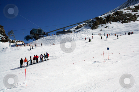 Skiers on alpine ski slope stock photo, Group of skiers on snowy alpine ski slope, Switzerland. by Martin Crowdy