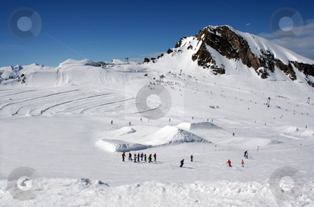 Alpine skiers landscape stock photo, Scenic landscape of skiers in Alpine mountains with peak in background, Crans Montana, Switzerland, by Martin Crowdy
