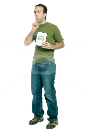 Movie Piracy stock photo, A young man dressed in casual clothing is holding a pirated movie and saying shhh, isolated against a white background. by Richard Nelson