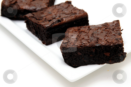 Chocolate Brownie stock photo, Sweet and tasty chocolate brownies served on a white rectangular plate against a light colored background by Lynn Bendickson