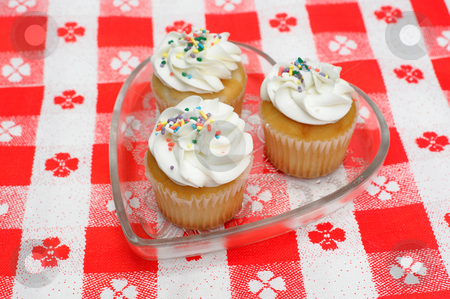 Cupcake With Sprinkles stock photo, Three cupcakes with white frosting and colorful sprinkles served in heart shaped dish on a red and white table cloth by Lynn Bendickson