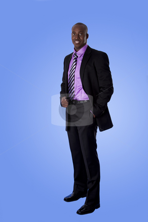 Happy African American business man stock photo, Handsome happy African American corporate business man smiling, wearing black suit with purple shirt, standing with authority with hand in pocket,  isolated. by Paul Hakimata