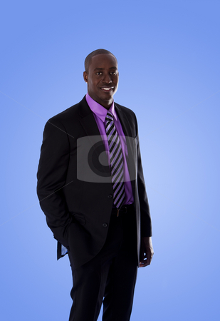 Happy African American business man stock photo, Handsome happy African American corporate business man smiling, wearing black suit with purple shirt, standing with hand in pocket,  isolated. by Paul Hakimata