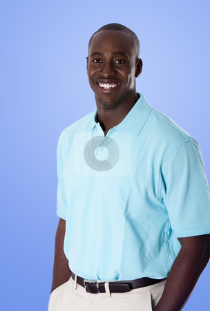 Happy African American business man stock photo, Handsome happy African American corporate business man smiling, wearing blue polo shirt, hands in pocket, standing, isolated. by Paul Hakimata