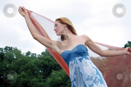 Beautiful Redhead Outdoors with Sheer Fabric (3) stock photo, A lovely young redhead outdoors with some sheer fabric blowing in the breeze and trees in the background.  Low angle. by Carl Stewart