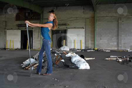 Beautiful Redhead with a Shovel (3) stock photo, A lovely young redhead with a shovel in front of a pile of garbage at a long-abandoned warehouse facility. by Carl Stewart