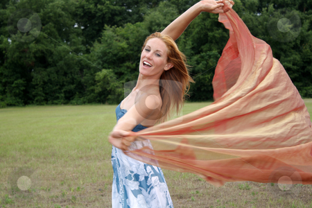 Beautiful Redhead Outdoors with Sheer Fabric (2) stock photo, A lovely young redhead outdoors with some sheer fabric blowing in the breeze. by Carl Stewart