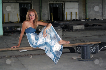 Beautiful Redhead at an Abandoned Warehouse (1) stock photo, A lovely young redhead sits on a makeshift bench at a long-abandoned warehouse facility. by Carl Stewart