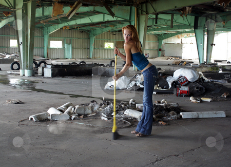Beautiful Redhead with a Broom (3) stock photo, A lovely young redhead with a broom in front of a pile of garbage at a long-abandoned warehouse facility. by Carl Stewart