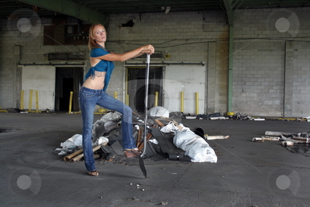 Beautiful Redhead with a Shovel (1) stock photo, A lovely young redhead with a shovel in front of a pile of garbage at a long-abandoned warehouse facility. by Carl Stewart