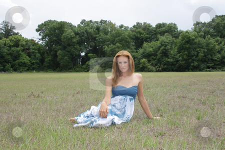 Beautiful Redhead in an Open Field (2) stock photo, A lovely young redhead sits in an open field outdoors.  A child-like drawing of a house with flowers has been added. by Carl Stewart