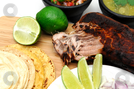 Mexican Carnitas stock photo, Pork roast cooked to make Mexican carnitas with fresh tortilla's' chunky tomato salsa and salsa verde and sliced limes by Lynn Bendickson