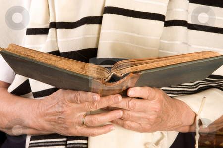 Jewish prayer stock photo, Hands holding a jewish prayer book wearing a prayer shawl by Anneke