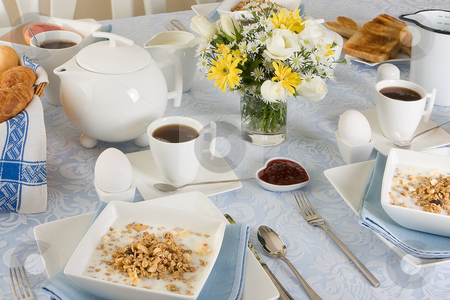 Sunny morning breakfast stock photo, Elegant breakfast table with cereals, eggs, flowers and toast by Anneke