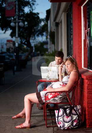 Pregnant woman ignored by partner stock photo, Pregnant woman sitting outside with annoying partner on computer next to her by Scott Griessel