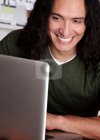 Smiling Native American man working on a laptop stock photo, Smiling Native American male working on a laptop by Scott Griessel