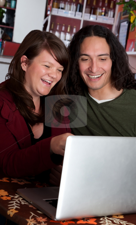 Couple with laptop laughing stock photo, Interracial couple on a laptop at a coffee house by Scott Griessel