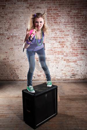 Female rocker stock photo, Young punk rocker on a speaker in front of a brick background by Scott Griessel