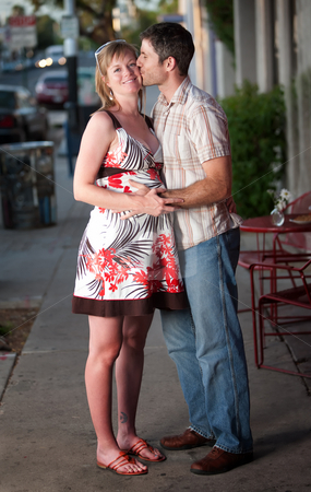 Loving family stock photo, Pregnant woman kissed by her partner on the street by Scott Griessel