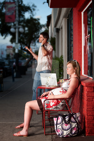 Pregnant woman sitting outside being ignored stock photo, Pregnant woman sitting outside being ignored by partner by Scott Griessel