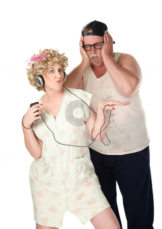 Wife listening to music stock photo, Wife listening to music while husband covers his ears by Scott Griessel