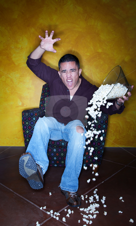Hispanic sports fan with popcorn watching television stock photo, Male Hispanic sports fan with popcorn watching television by Scott Griessel