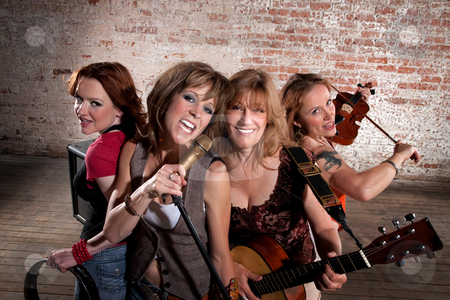 Female musicians stock photo, All-girl band performing in stylish clothing at a warehouse by Scott Griessel