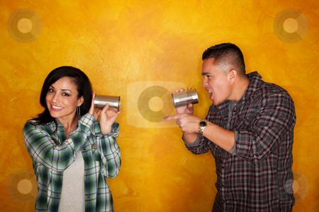 Hispanic man and woman communicate through tin cans stock photo, Attractive Hispanic man and woman communicate through tin cans by Scott Griessel