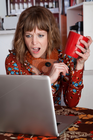 Shocked brunette stock photo, Shocked brunette reading email and holding red mug at a cafe by Scott Griessel