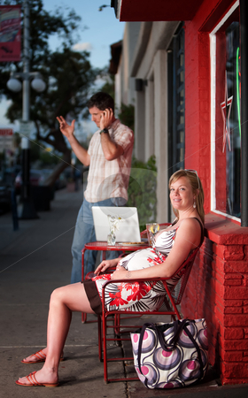 Pregnant woman sitting stock photo, Pregnant woman sitting while man talks on his phone by Scott Griessel