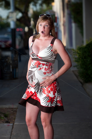 Pregnant woman experiencing birth pains stock photo, Pregnant woman experiencing birth pains while walking on the sidewalk by Scott Griessel
