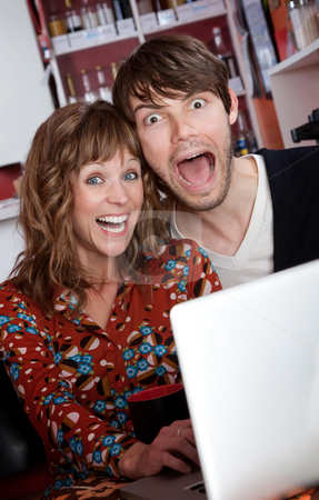 Happy young couple stock photo, Overjoyed young couple browsing the internet at a cafe by Scott Griessel
