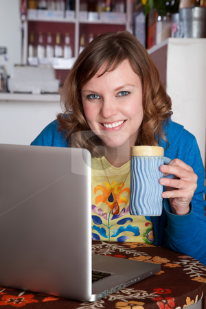 Pretty lady smiling stock photo, Pretty lady smiling with laptop at a cafe by Scott Griessel