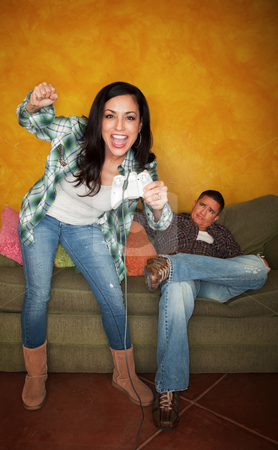 Hispanic man bored while wife plays video game stock photo, Attractive Hispanic woman playing video game while bored partner watches by Scott Griessel