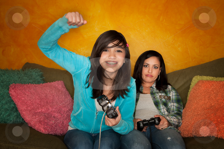 Hispanic Woman and Girl Playing Video game stock photo, Attractive Hispanic Woman and Girl Playing a Video Game with Handheld Controllers by Scott Griessel