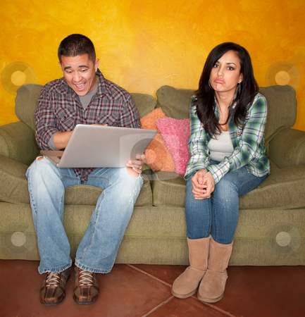 Hispanic Couple with Computer stock photo, Hispanic Couple on Green Couch with Computer Woman is Bored by Scott Griessel