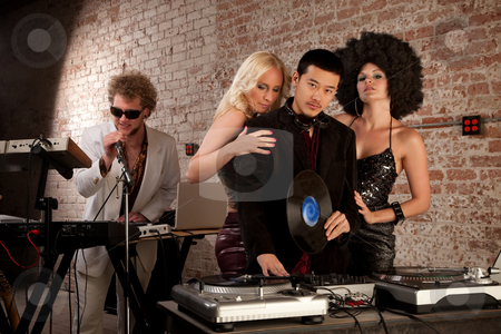 1970s Disco Music Party stock photo, Handsome Asian DJ and Caucasian singer with ladies by Scott Griessel