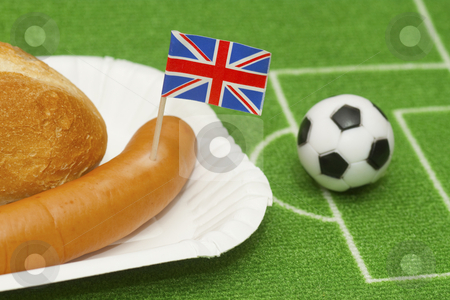 Soccer ball stock photo, Sausage with roll on a football field background with soccer ball by Birgit Reitz-Hofmann