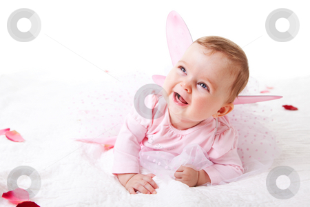 Toddler in a Fairy Outfit stock photo, A cute baby girl in fairy wings laughs while lying on the ground covered in flower petals.  Vertical shot. by Angela Hawkey