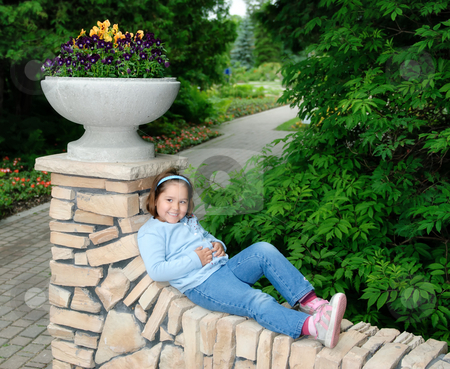 Relaxation stock photo, A young girl is lying on a stone fence, relaxing in the sun by Richard Nelson