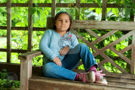 Day Dreaming stock photo, A little girl sitting on a park bench is day dreaming about something. by Richard Nelson