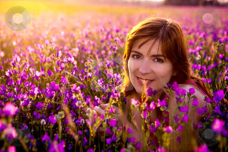 Enjoy the nature stock photo, Beautiful young woman portrait on a flowery meadow by ikostudio