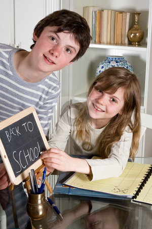 Back to school stock photo, Two teenagers writing Back to School on a small blackboard by Anneke