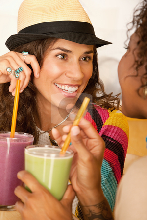 Women Talking Over Smoothies stock photo, Two women are talking and enjoying smoothies together.  Vertical shot. by Scott Griessel